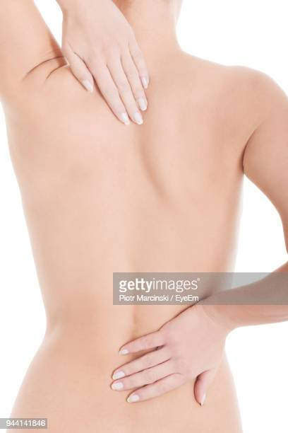 Rear View Of Shirtless Woman With Backache Against White Background