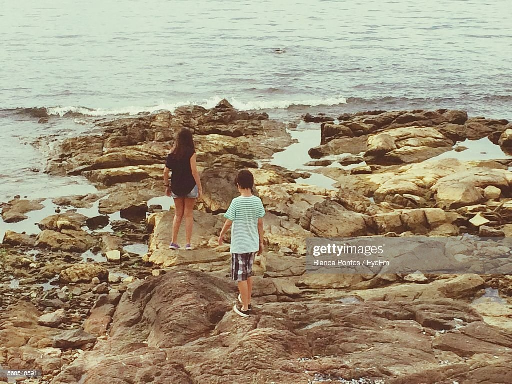 Rear View Of Sibling Walking On Rocks By Water : Stock Photo