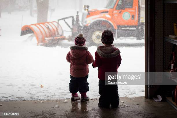 rear view of siblings in warm clothing standing at store entrance - snowplow stock pictures, royalty-free photos & images