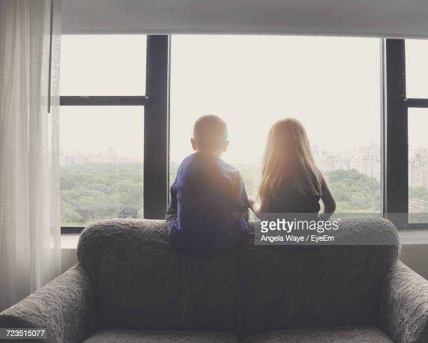 rear view of siblings looking through window while sitting on sofa at home - zus stockfoto's en -beelden