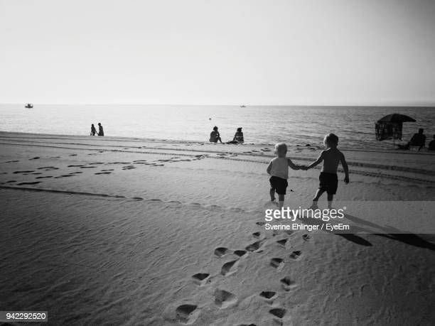 rear view of siblings on sand at beach against clear sky - heldere lucht stockfoto's en -beelden