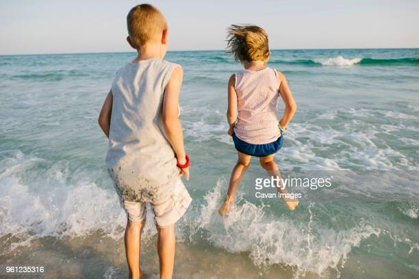 rear view of siblings playing with waves at beach - destin beach stock pictures, royalty-free photos & images