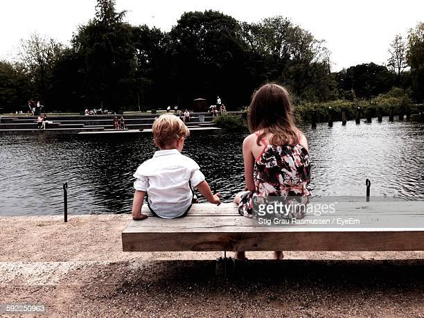rear view of siblings sitting on bench at riverbank - funen stock pictures, royalty-free photos & images