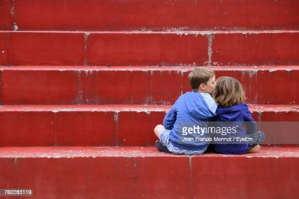 rear view of siblings sitting on steps - amour photos et images de collection