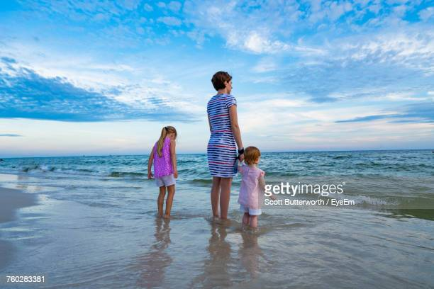 Rear View Of Siblings Standing On Beach Against Sky