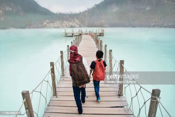 rear view of siblings walking on pier over lake - bandung stock pictures, royalty-free photos & images