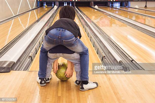 Rear View Of Siblings With Ball In Front Of Bowling Alley