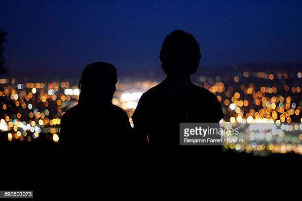 Rear View Of Silhouette Couple Against Illuminated City At Night