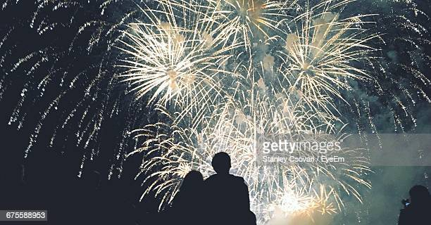 rear view of silhouette couple looking at firework display at night - fireworks stock pictures, royalty-free photos & images