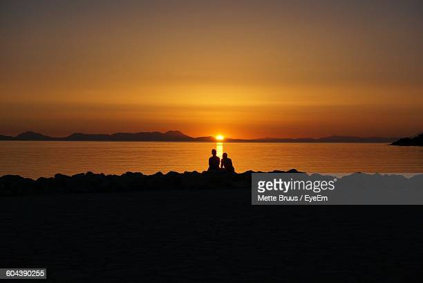 Rear View Of Silhouette Couple Overlooking Calm Sea At Sunset