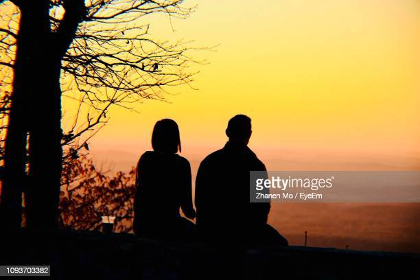 Rear View Of Silhouette Couple Sitting Against Orange Sky
