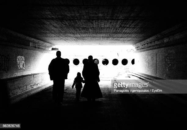 rear view of silhouette family walking under bridge - vgenopoulos stock pictures, royalty-free photos & images