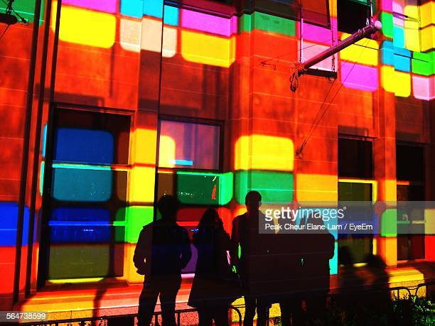 Rear View Of Silhouette Friends Standing In Front Of Colorful Building At Night