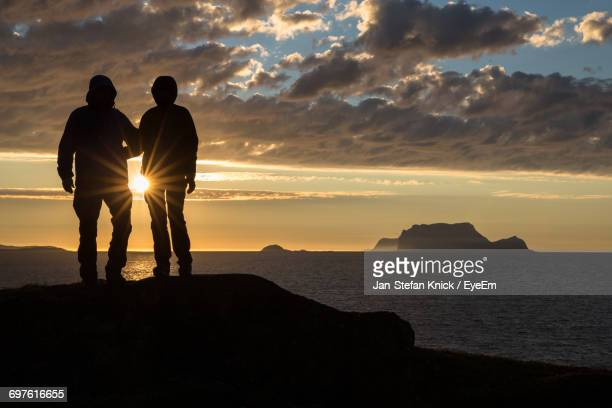 Rear View Of Silhouette Friends Standing On Rock By Sea Against Sky During Sunset