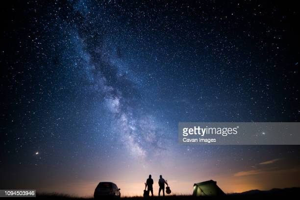 rear view of silhouette friends with guitars standing on field against star field at campsite - stars and strings stock photos and pictures
