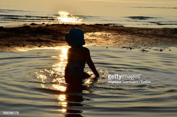 Rear View Of Silhouette Girl Sitting In Water At Beach During Sunset