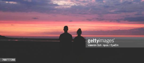 Rear View Of Silhouette Man And Woman Standing On Landscape Against Orange Sky
