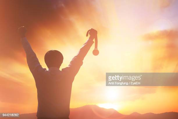 Rear View Of Silhouette Man Arms Raised With Medal Against Orange Sky