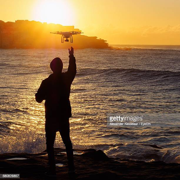 Rear View Of Silhouette Man Controlling Quadcopter At Beach Against Sky