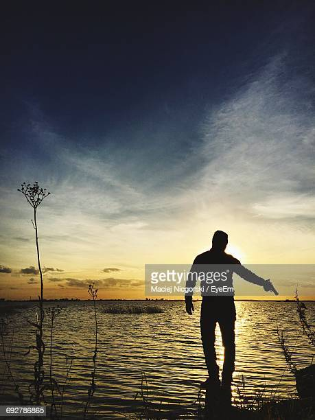 rear view of silhouette man holding gun in sea against sky during sunset - pistolet photos et images de collection