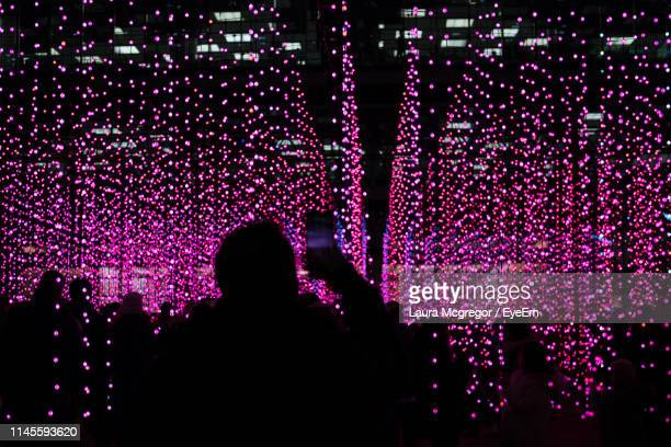 rear view of silhouette man photographing illuminated pink lights at night - arts culture and entertainment stock pictures, royalty-free photos & images