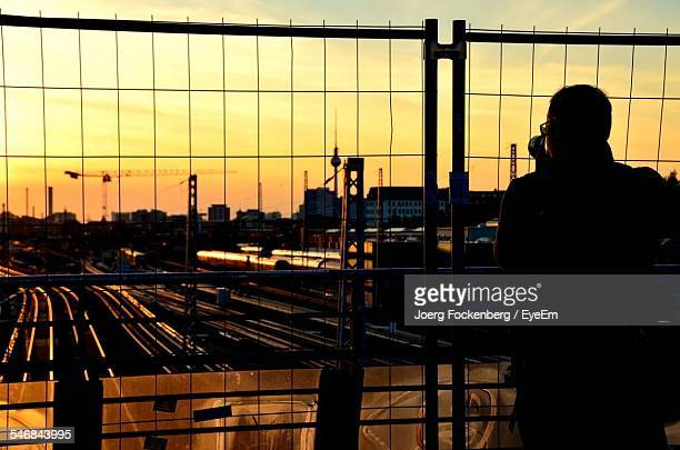 Rear View Of Silhouette Man Photographing Railroad Junction By Chainlink Fence