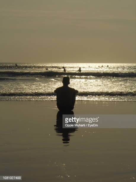 rear view of silhouette man sitting at beach against sky during sunset - oppie muharti stock pictures, royalty-free photos & images
