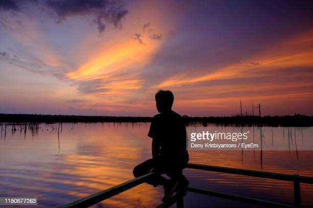 Rear View Of Silhouette Man Sitting On Railing By Lake Against Sky During Sunset