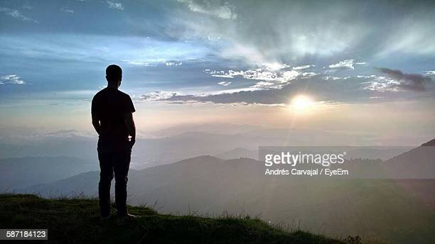 rear view of silhouette man standing against mountain range during sunset - carvajal ストックフォトと画像