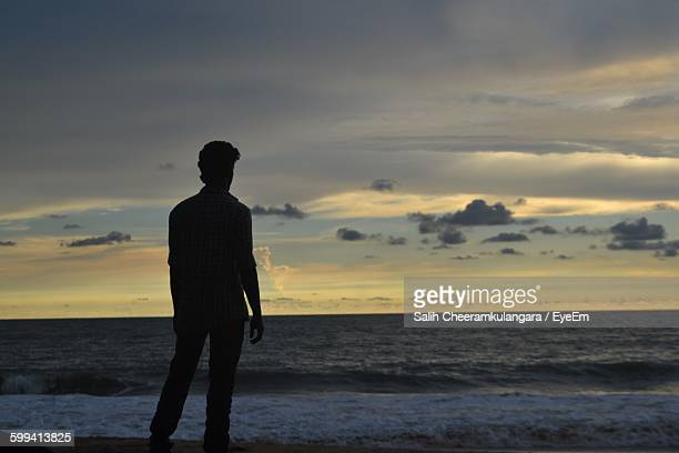 Rear View Of Silhouette Man Standing Against Sea During Sunset