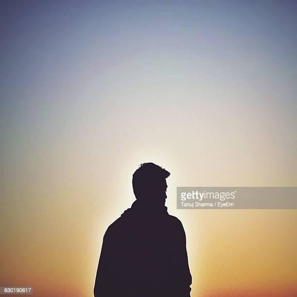 rear view of silhouette man standing against sky during sunset - back lit stock pictures, royalty-free photos & images