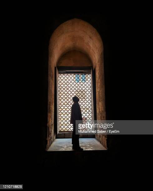rear view of silhouette man standing against window - middle east stock pictures, royalty-free photos & images