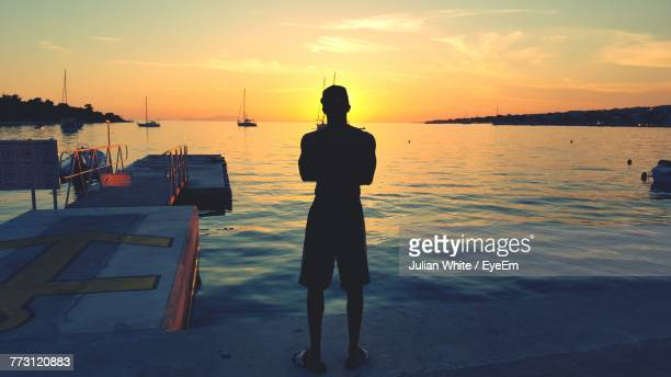 Rear View Of Silhouette Man Standing At Beach Against Sky During Sunset