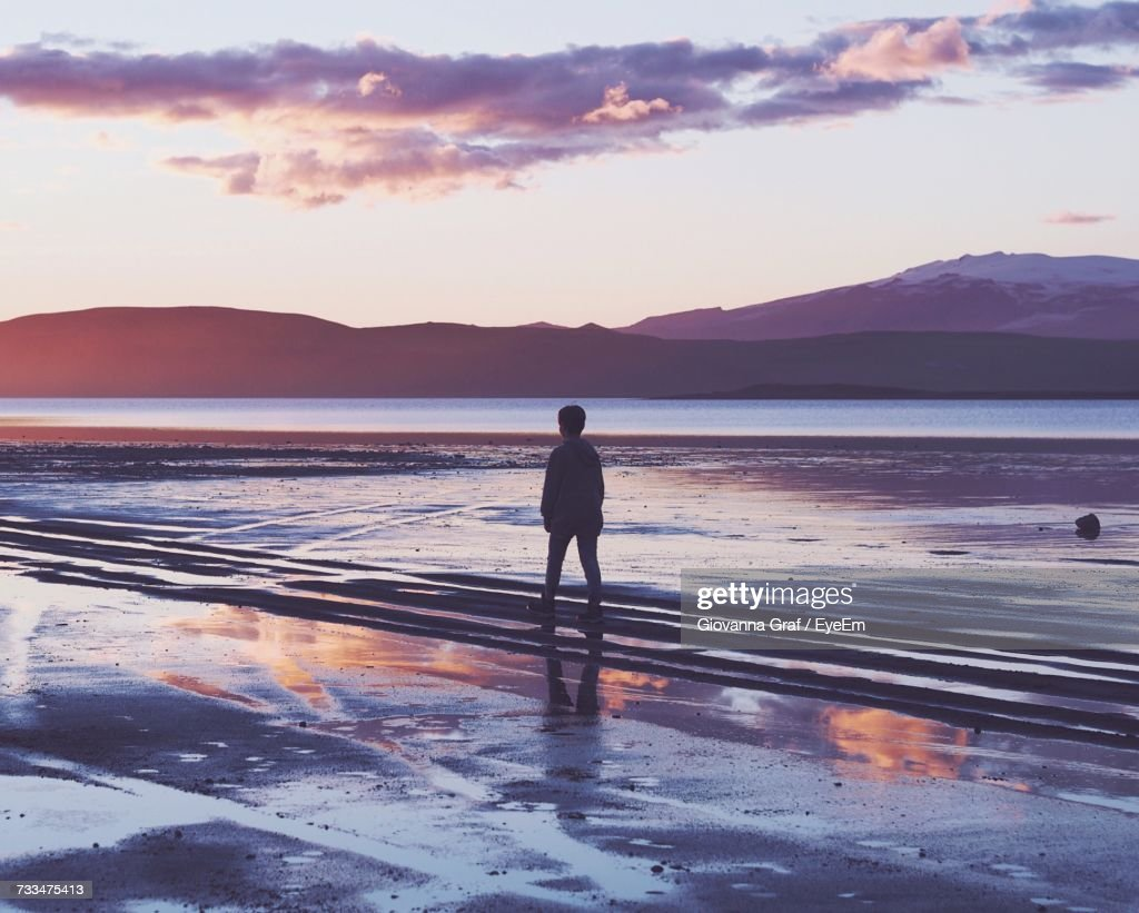 Rear View Of Silhouette Man Standing At Beach Against Sky : Stock Photo