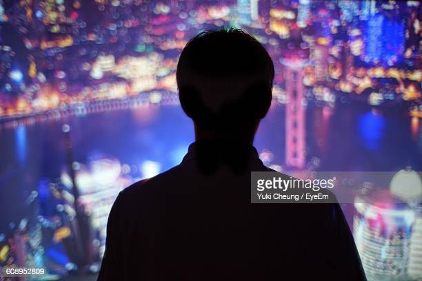 rear view of silhouette man standing in from of cityscape at night - unrecognizable person stock pictures, royalty-free photos & images