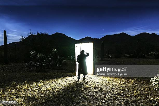 Rear View Of Silhouette Man Standing In Front Of Illuminated Door On Field Against Sky At Dusk