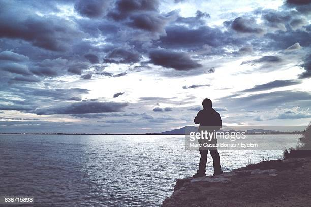 Rear View Of Silhouette Man Standing On Cliff In Front Of Sea At Dusk