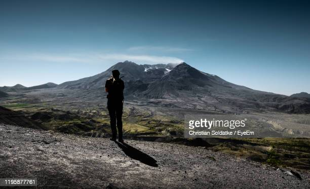 rear view of silhouette man standing on mountain against sky - christian soldatke stock pictures, royalty-free photos & images