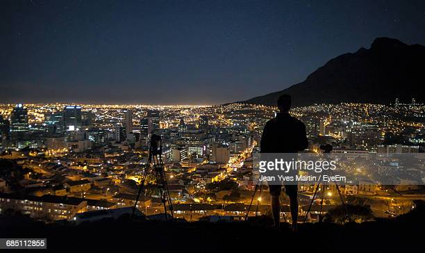 Rear View Of Silhouette Man Standing With Tripods Against Illuminated Cityscape