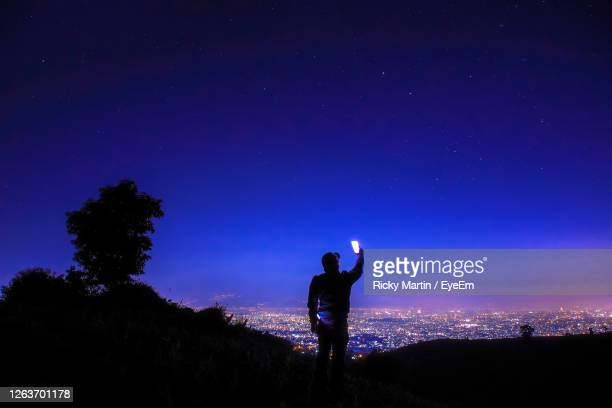 rear view of silhouette man taking selfie on mountain against blue sky at night - astronomy stock pictures, royalty-free photos & images
