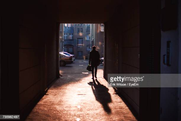 rear view of silhouette man walking at doorway during sunset - doorway stock pictures, royalty-free photos & images