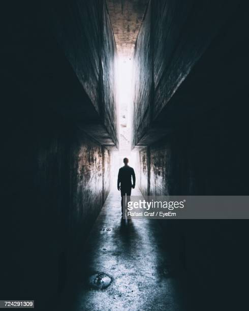rear view of silhouette man walking in tunnel - shadow forms stock photos and pictures