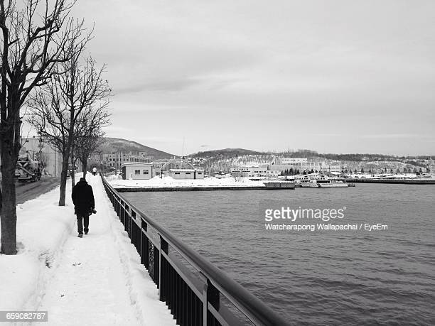 rear view of silhouette man walking on snowcapped bridge during winter - 小樽市 ストックフォトと画像