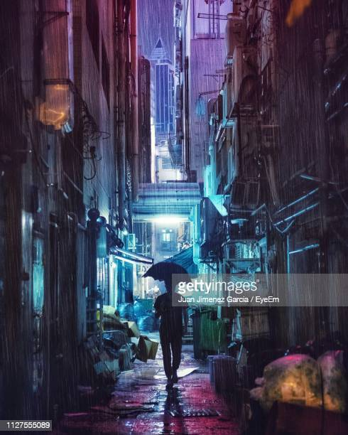 rear view of silhouette man walking with umbrella in alley at night during rain - 路地 ストックフォトと画像