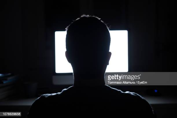rear view of silhouette man watching television at home - back lit stock pictures, royalty-free photos & images