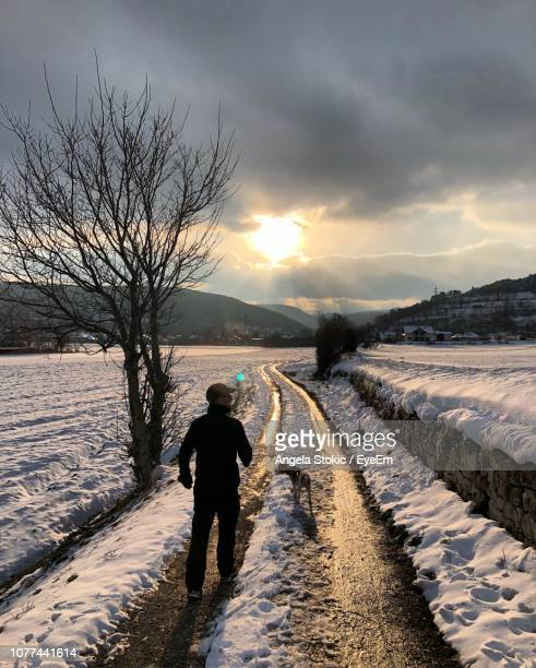Rear View Of Silhouette Man With Dog Walking On Snow Covered Road During Sunrise