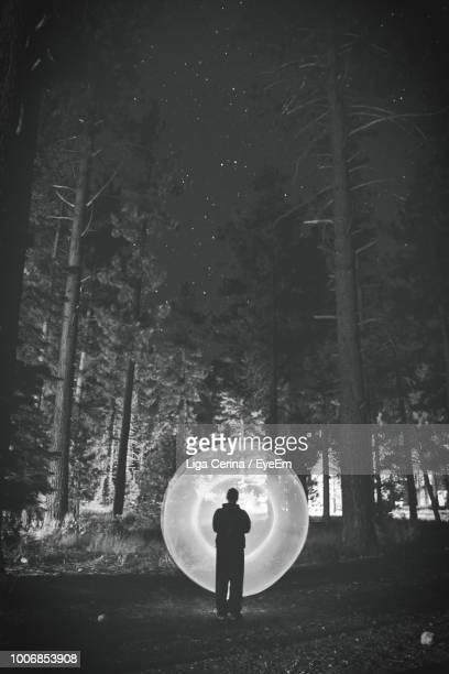 rear view of silhouette man with wire wool standing in forest at night - liga cerina stock pictures, royalty-free photos & images