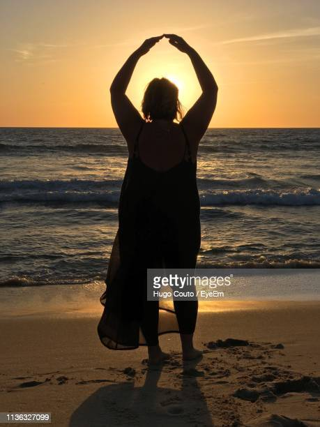 rear view of silhouette mature woman with arms raised standing on beach against sky during sunset - comporta portugal fotografías e imágenes de stock