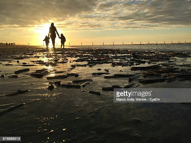 Rear View Of Silhouette Mother With Sons Walking At Beach Against Sky During Sunset