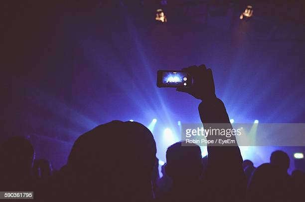 Rear View Of Silhouette Person Photographing During Music Concert